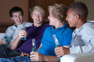 Group Of Teenage Boys Sitting On Sofa At Home Watching Drinking